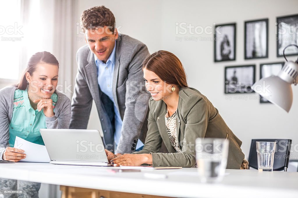 Young business people using laptop at table in office stock photo