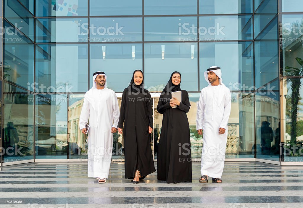 Young business people walking out of glass building stock photo
