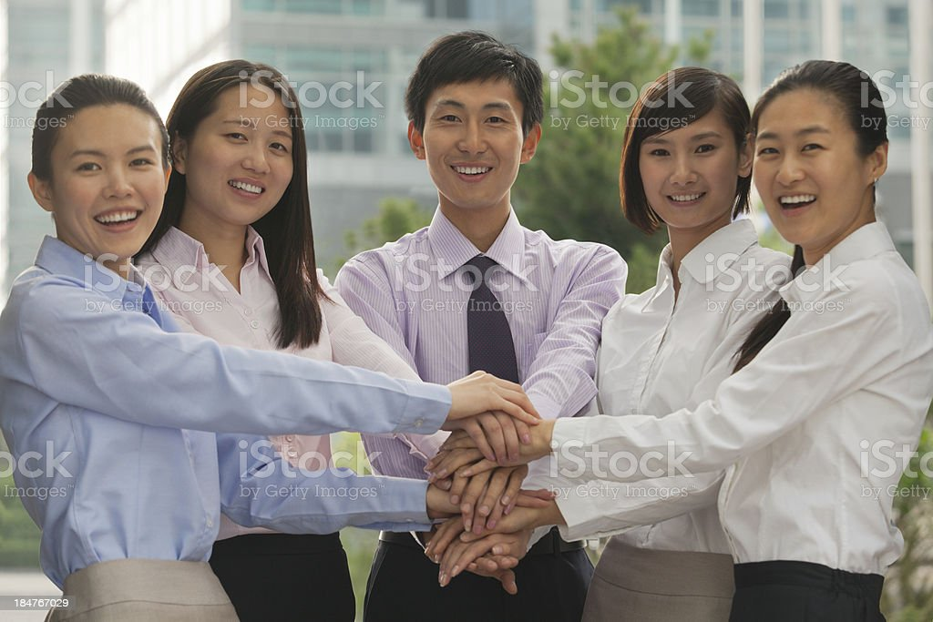 Young business people with hands on top of each other royalty-free stock photo