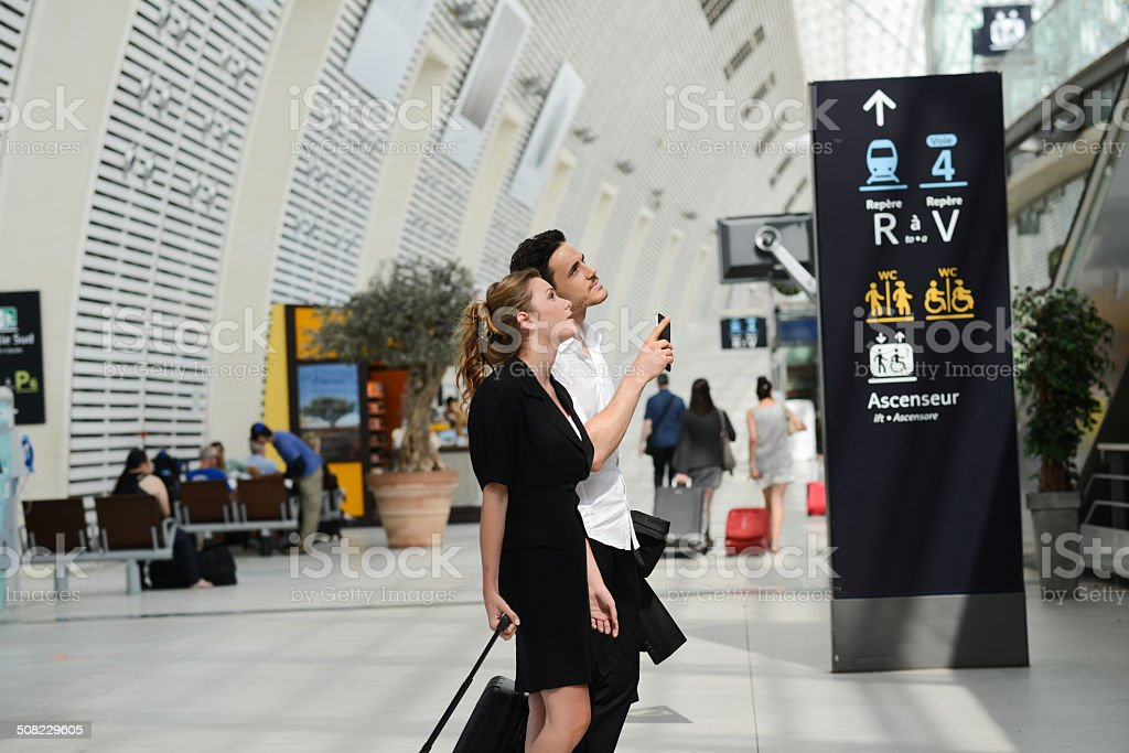 young business travelers man woman public station looking for schedule stock photo