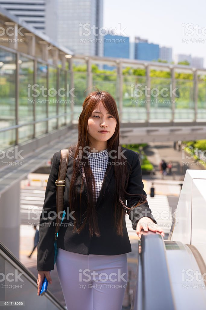 Young business woman ascending escalator outside stock photo