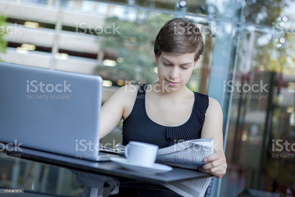 Young business woman enjoying her morning coffee and reading newspaper royalty-free stock photo