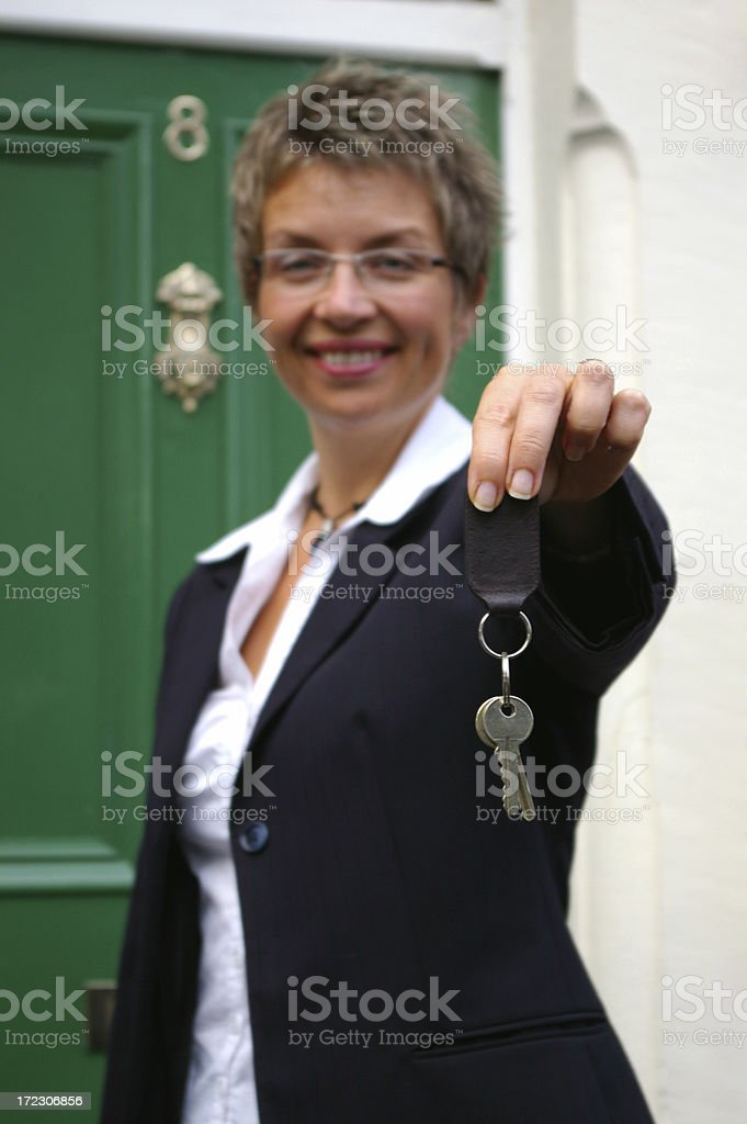 Young business woman handing over the keys to a property royalty-free stock photo