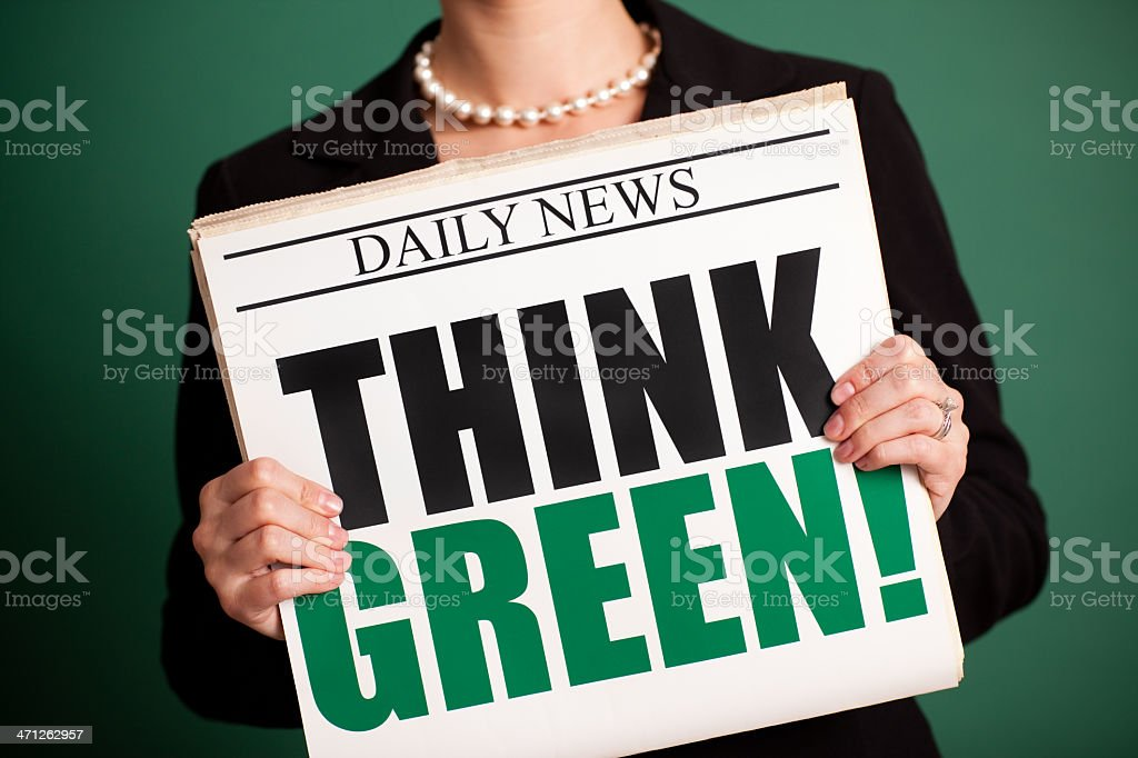 Young Business Woman Holding Newspaper Headlined 'Think Green!' royalty-free stock photo