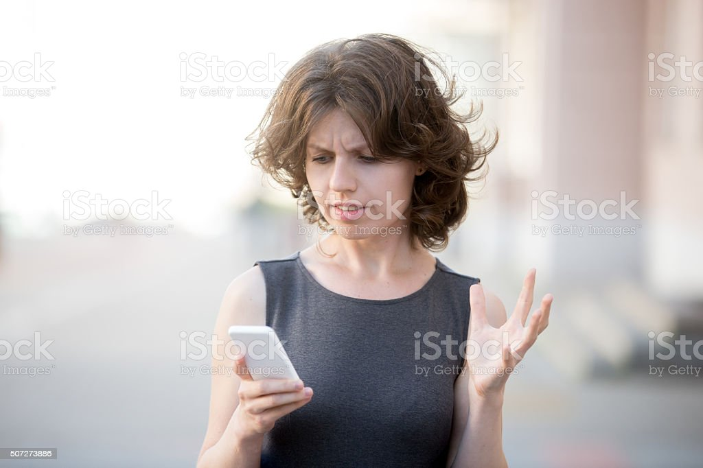 Young business woman irritated with her phone stock photo