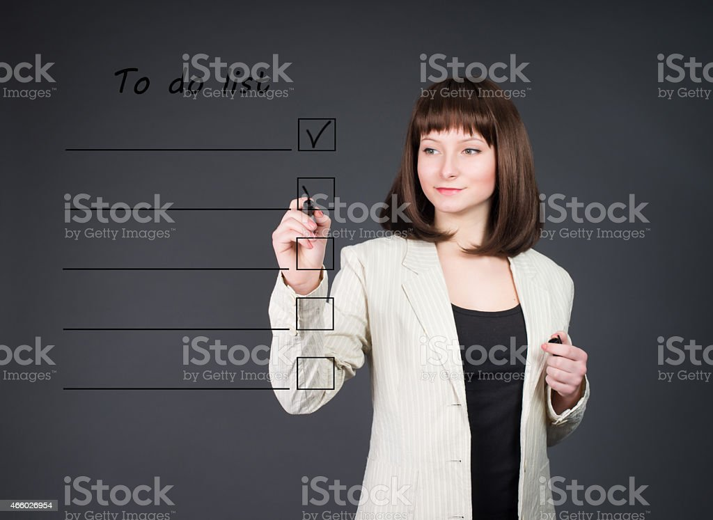 Young business woman listing to do list. Time management. stock photo