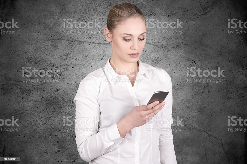 Young business woman looking down at her smartphone pensively stock photo