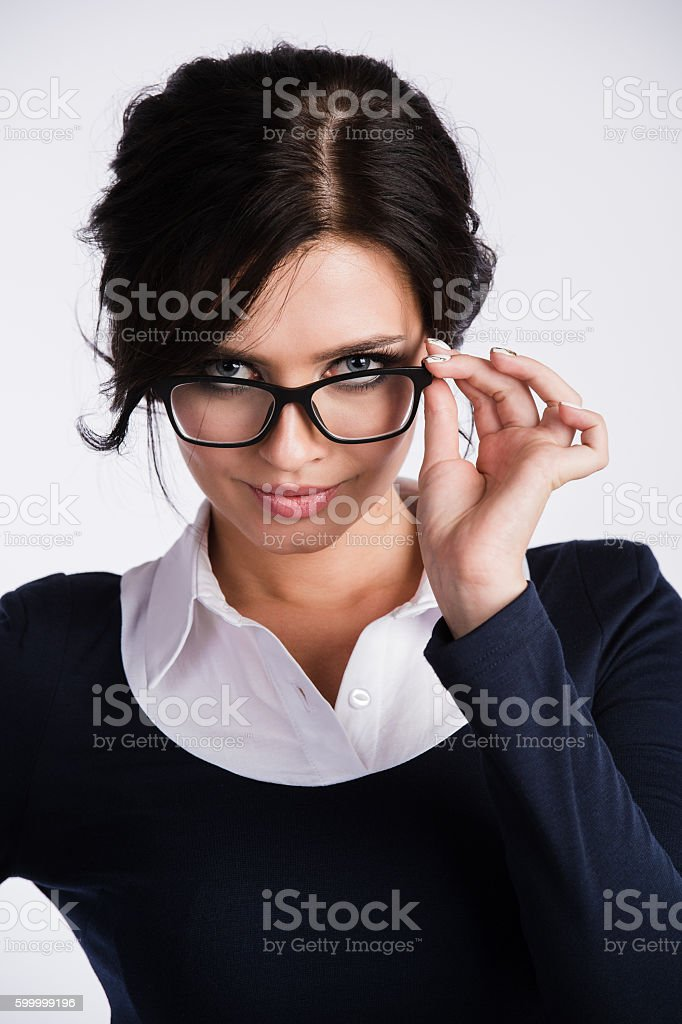 Young business woman looking skeptically over her spectacles, on white stock photo