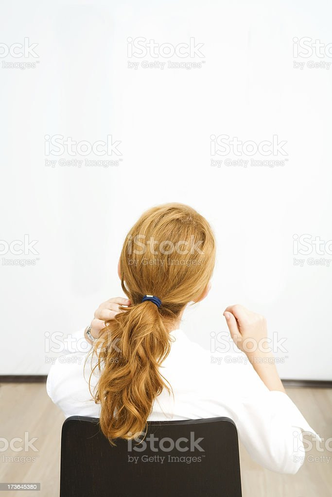 Young business woman looking to a white board (copy-space) royalty-free stock photo