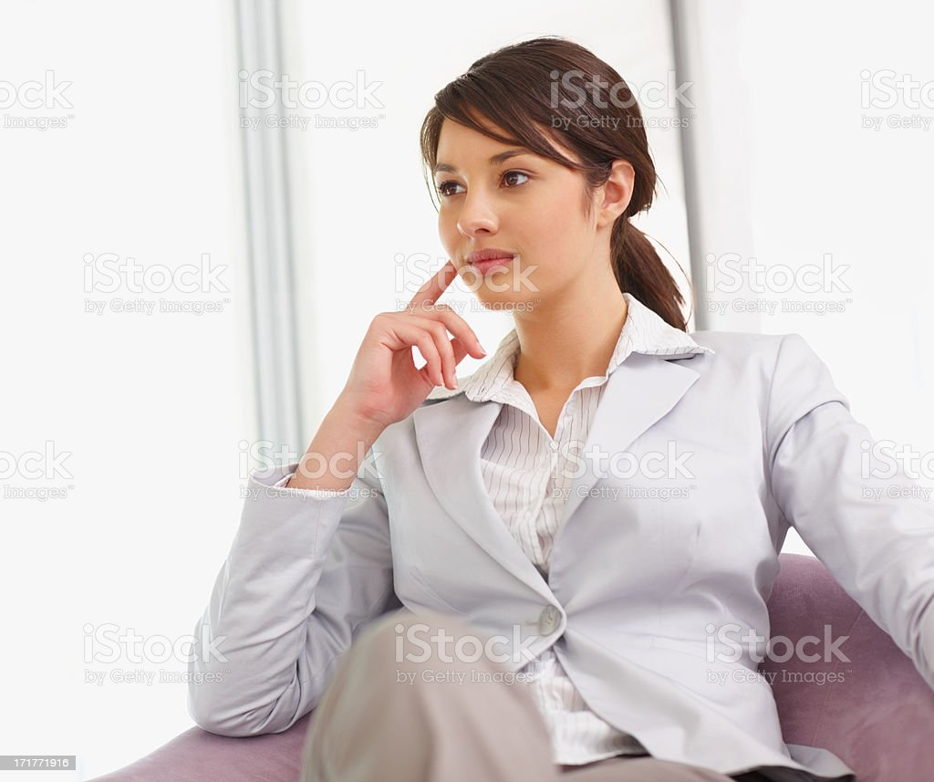 Young business woman lost in thought , sitting on a chair stock photo
