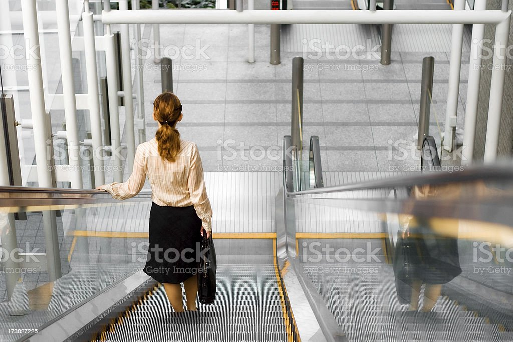 Young business woman on stairs (leaving office) royalty-free stock photo