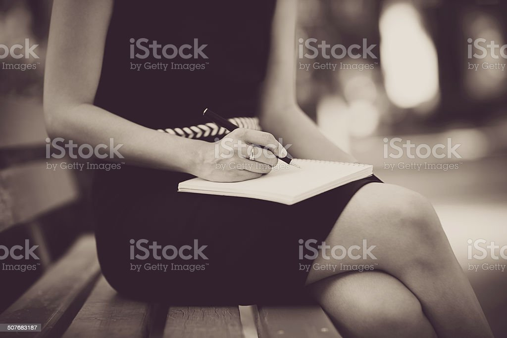 Young business woman planing, writing and reviewing report at ci stock photo