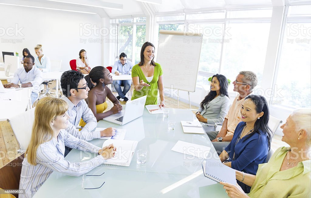 Young Business Woman Presenting to her Colleagues stock photo