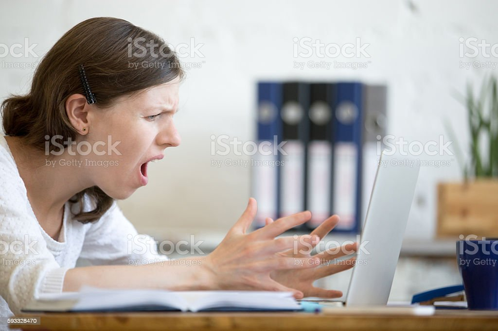 Young business woman screaming at laptop stock photo