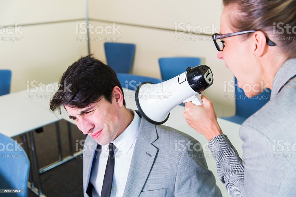 Young business woman screaming on her coworker with megaphone stock photo