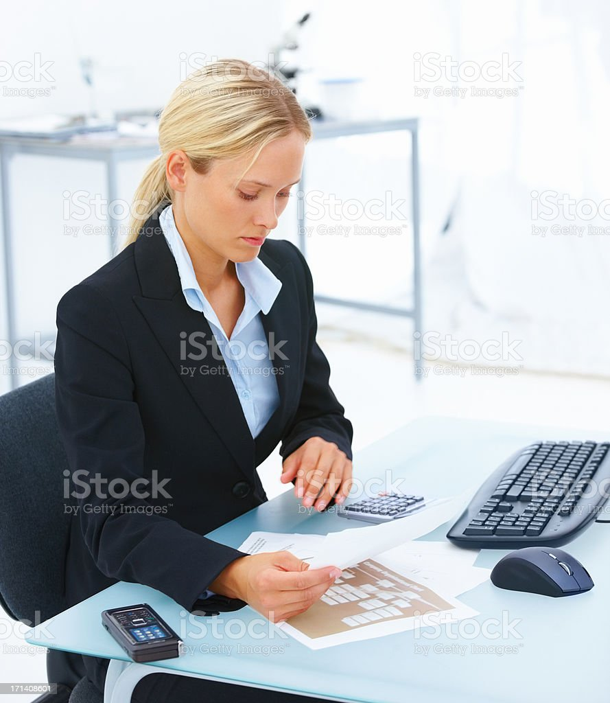 Young business woman sitting at office desk and reading a document royalty-free stock photo