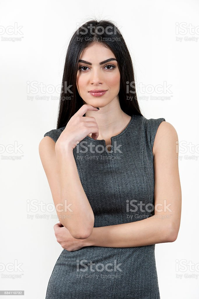 Young business woman standing with hand on chin. stock photo