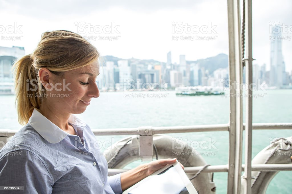 Young business woman using digital tablet on ferry boat stock photo