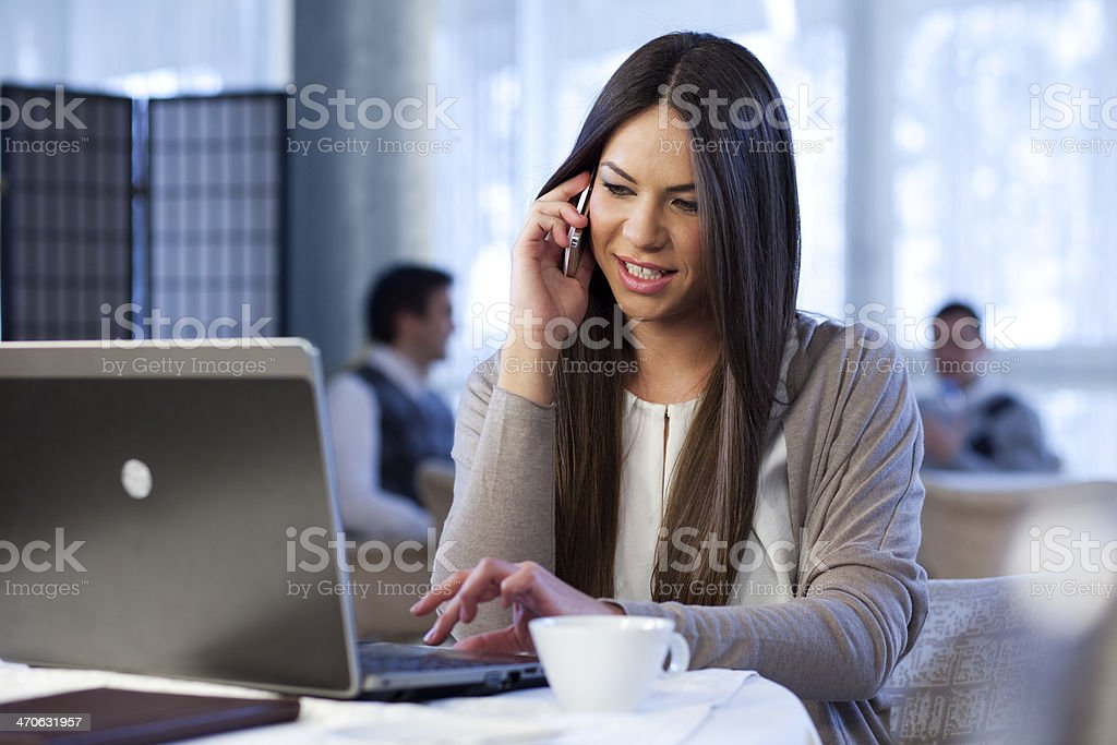 Young business woman using phone and computer at the caffe stock photo