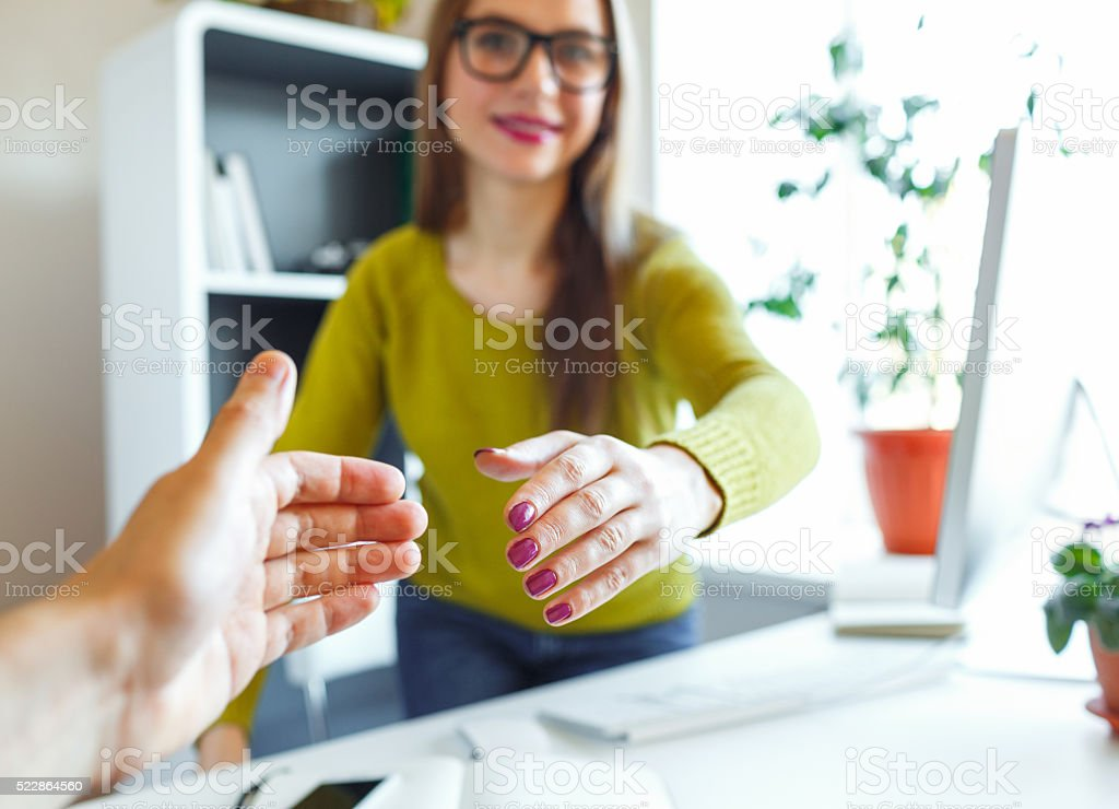 Young business woman with arm extended to handshake stock photo