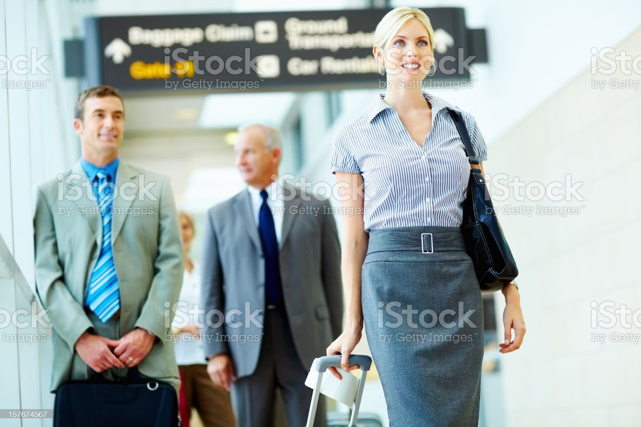 Young business woman with people in background at airport royalty-free stock photo