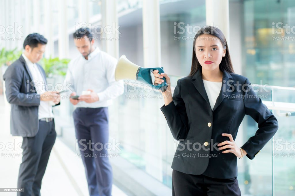 Young business woman working at the office holding megaphone. stock photo