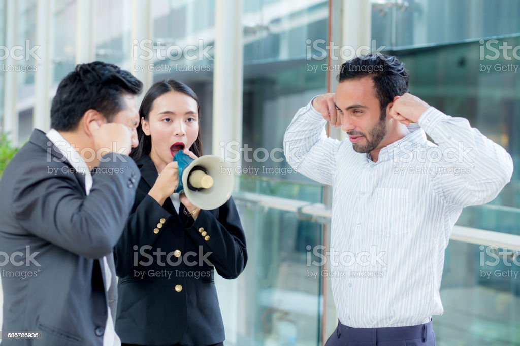 Young business woman working at the office, 'nshouting and yelling in megaphone stock photo