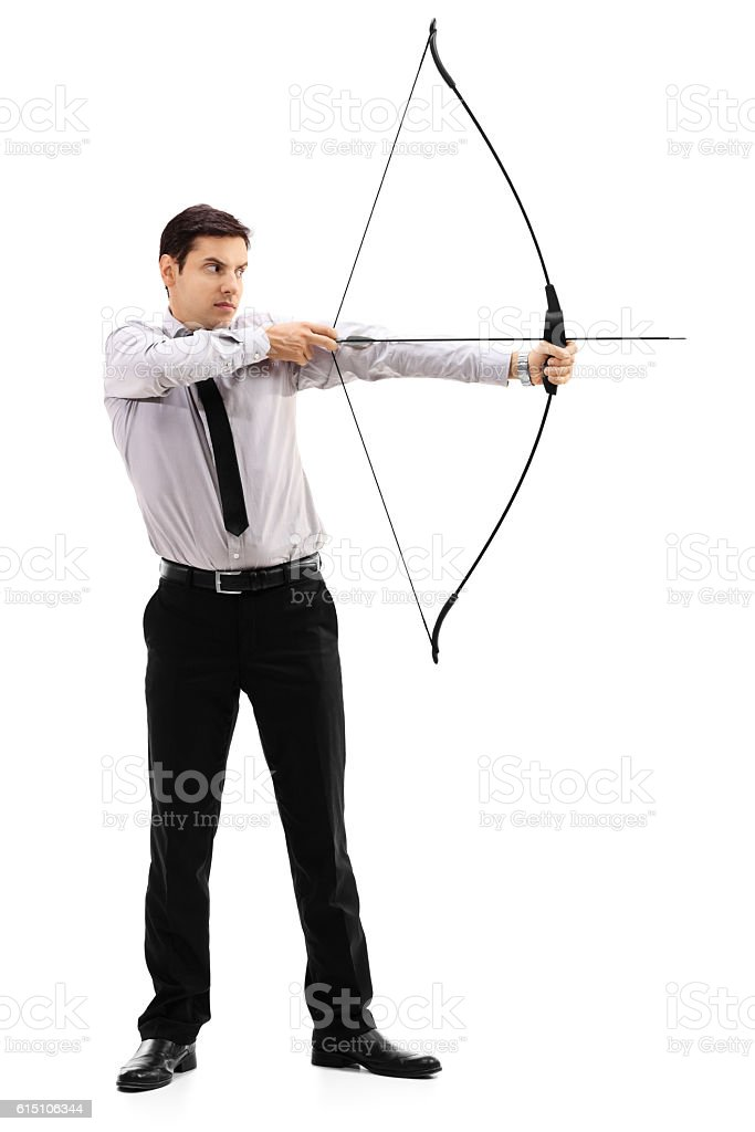 Young businessman aiming with a bow and arrow stock photo