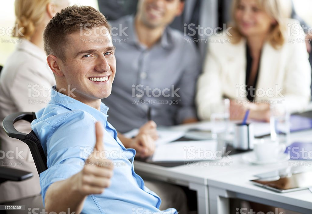 Young businessman among colleagues showing thumb up royalty-free stock photo