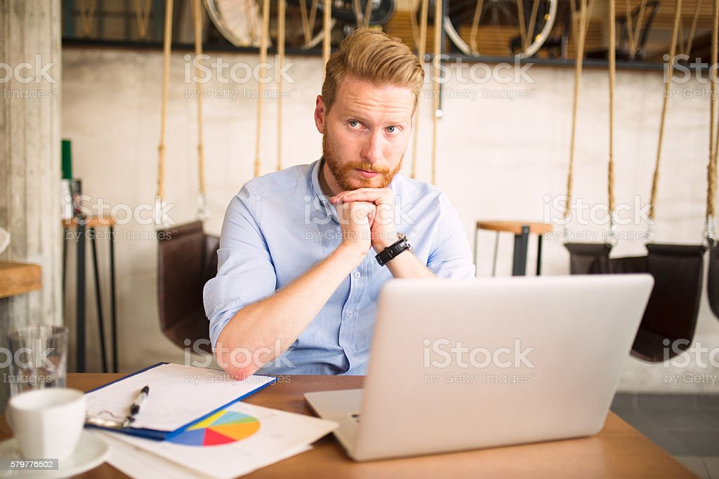 Young businessman analyzing graphs during coffee break. stock photo