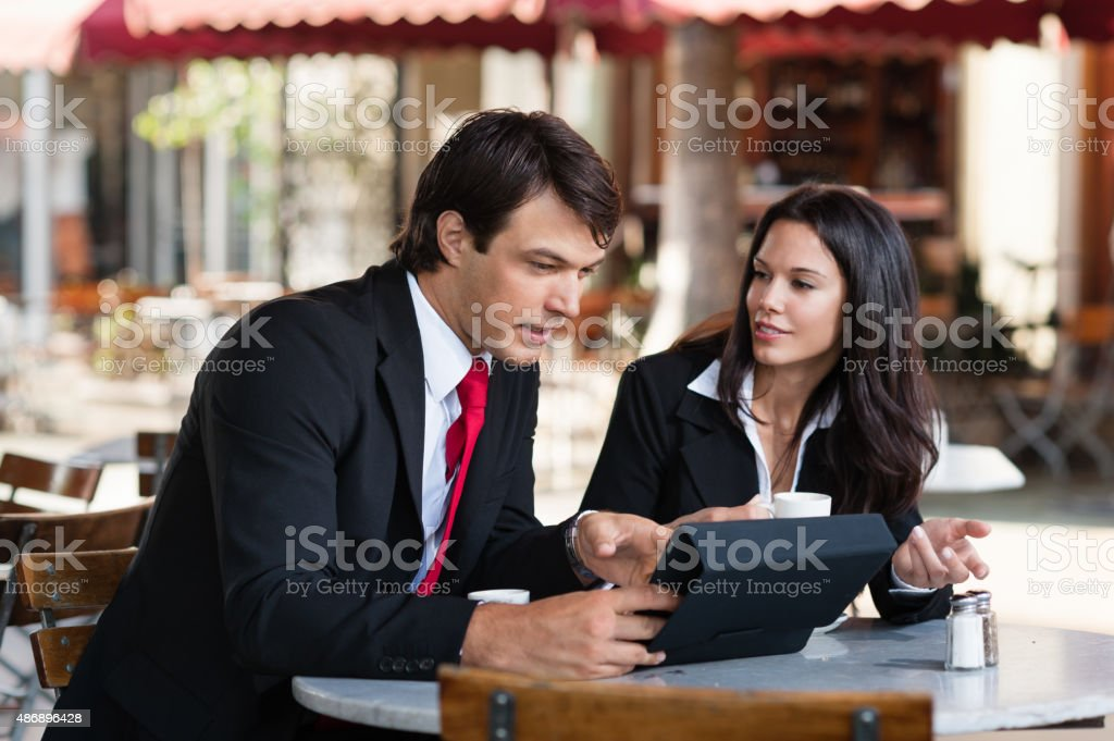 Young Businessman and Businesswoman Discussing Digital Tablet stock photo