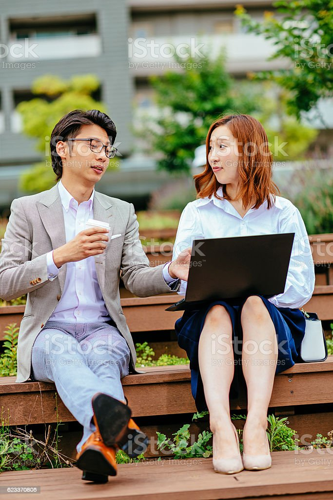 Young businessman and his coworker using laptop stock photo