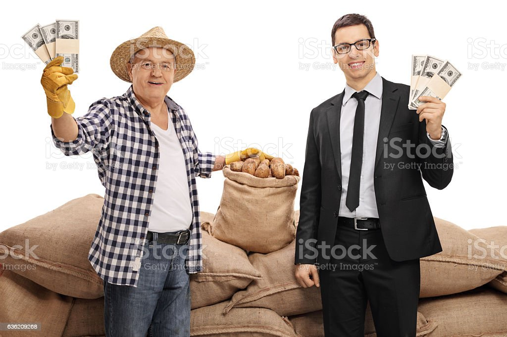 Young businessman and mature farmer holding money bundles stock photo