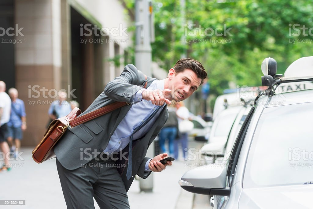 Young businessman asking address to Taxi driver stock photo