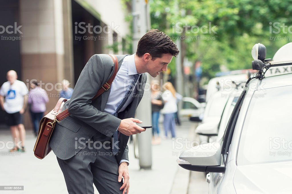 Young businessman asking an address to the taxi stock photo
