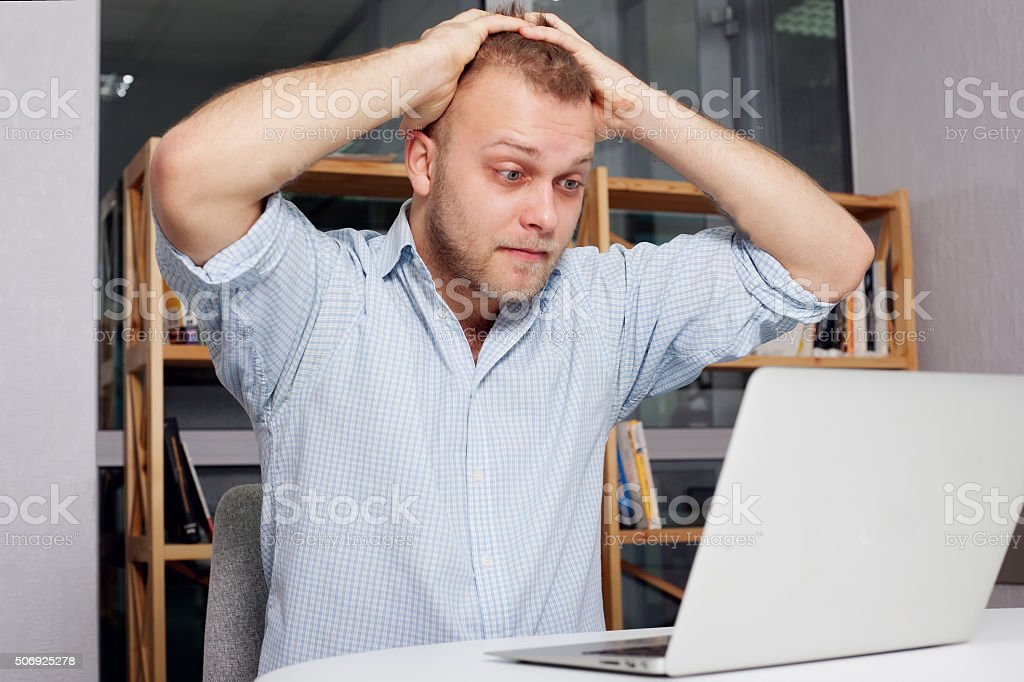 young businessman at his desk looking fearfully stock photo