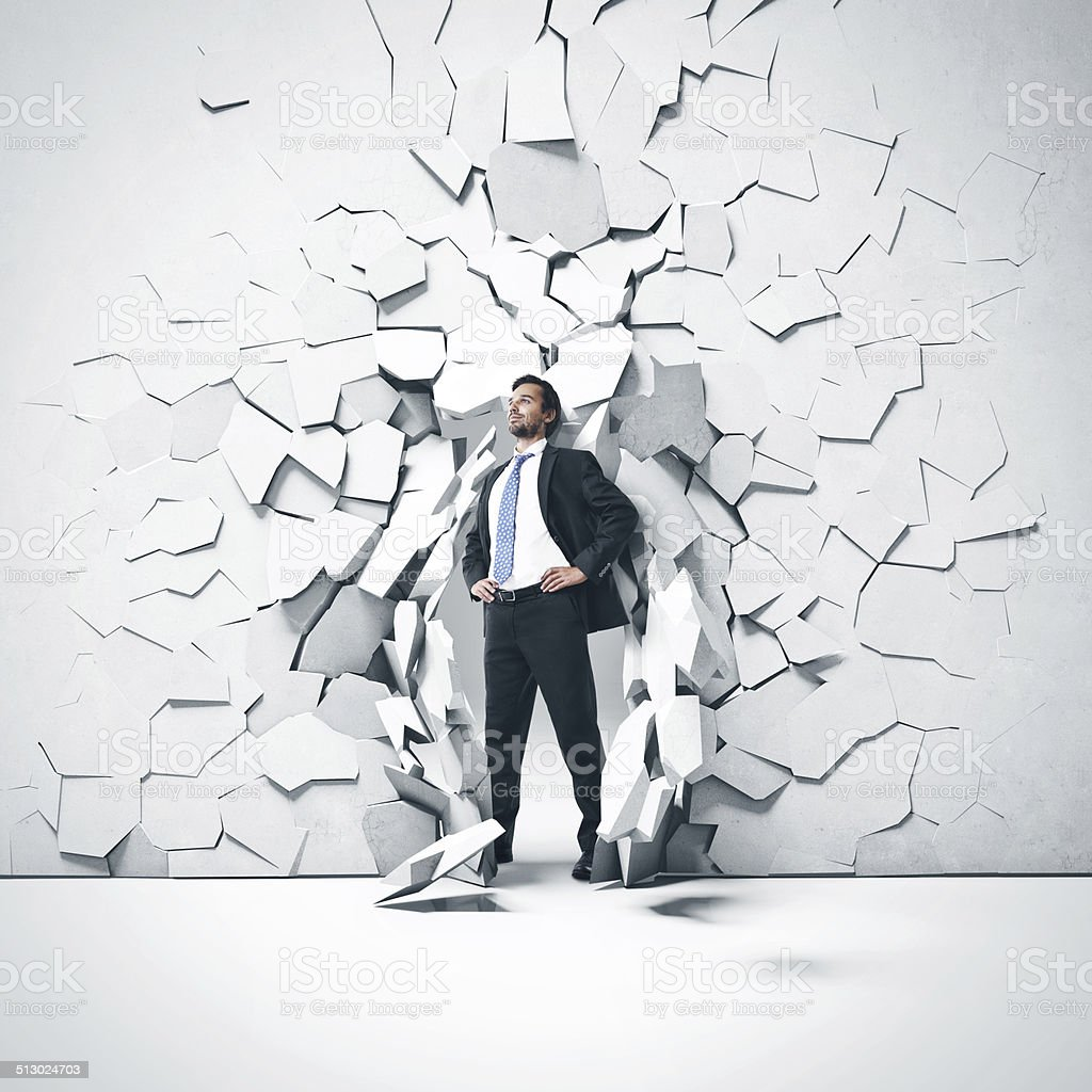 Young businessman breaking trough a wall stock photo