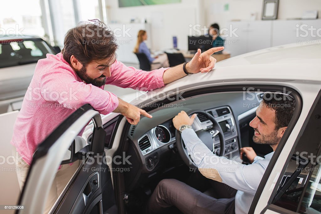 Young businessman buying new car and talking to car salesperson. stock photo
