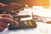 Young businessman calculating about cost and using smartphone se