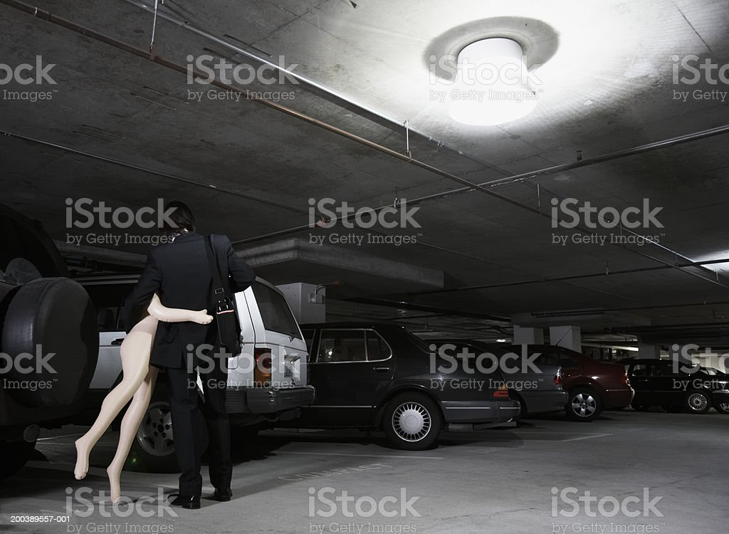 Young businessman carrying blow-up doll in parking garage, rear view stock photo