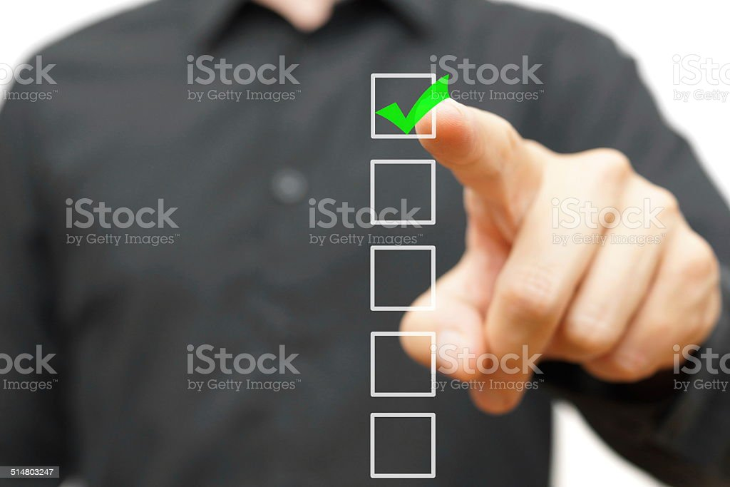 Young businessman checking mark on checklist with marker. stock photo