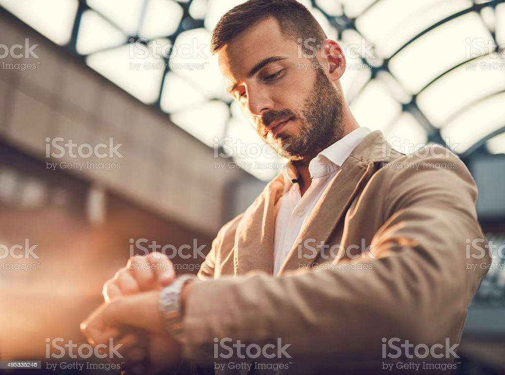 Young businessman checking the time on his wristwatch. stock photo
