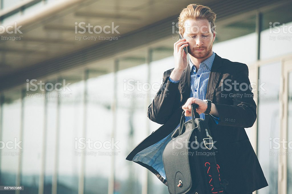 Young businessman checking time and talking on the cell phone stock photo