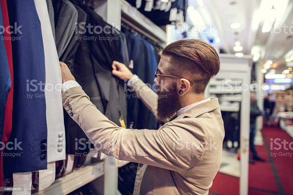 Young businessman choosing suits in a clothing store. stock photo