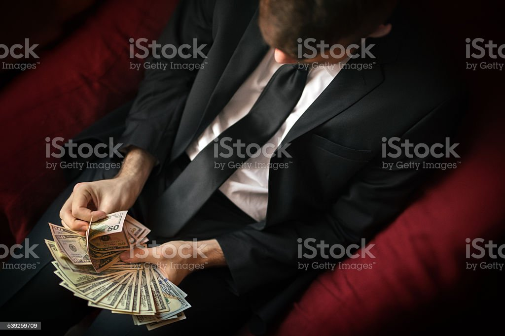 young businessman counting usa dollars stock photo