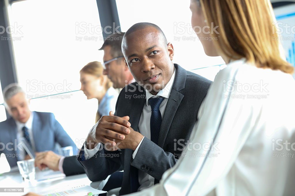 Young businessman discussing with female colleague in meeting room stock photo