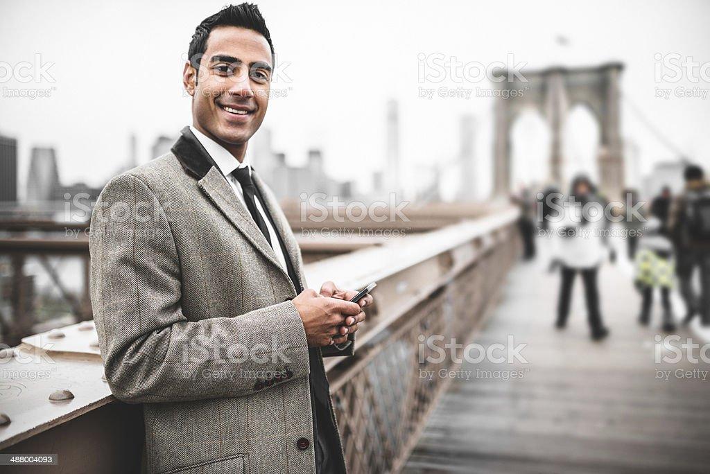 young Businessman entrepreneur messaging on the brooklyn bridge stock photo