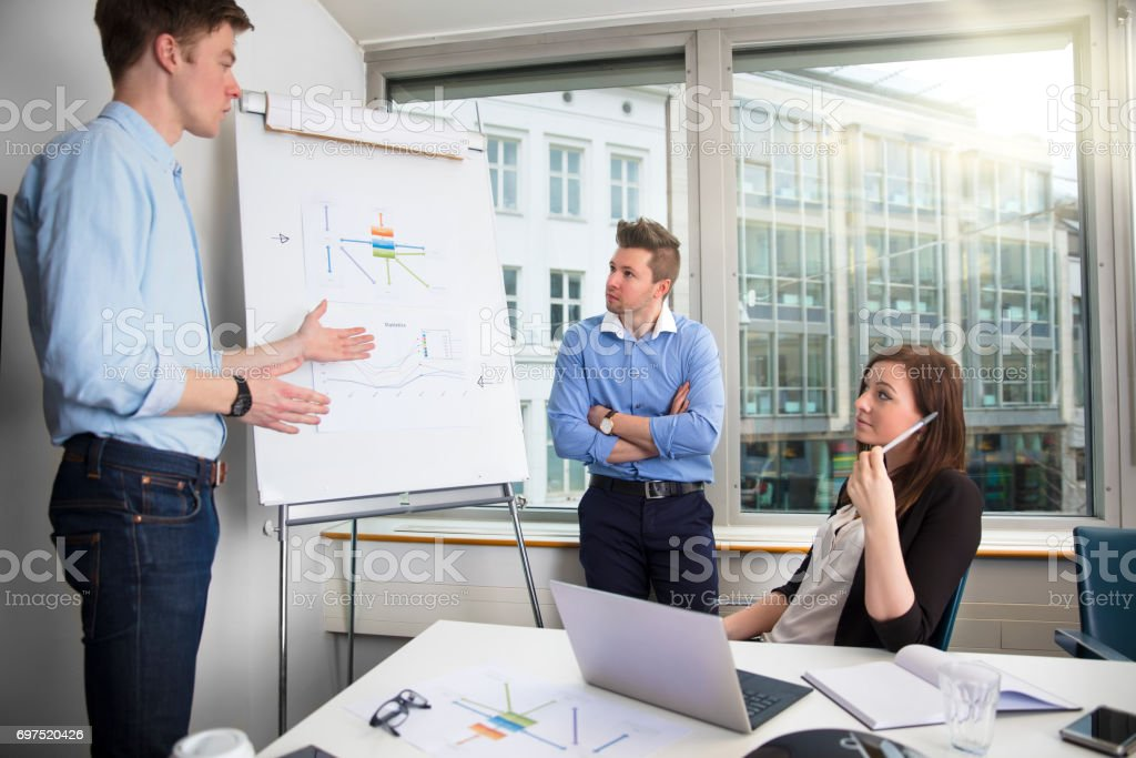 Young Businessman Explaining Chart To Male And Female Coworkers stock photo