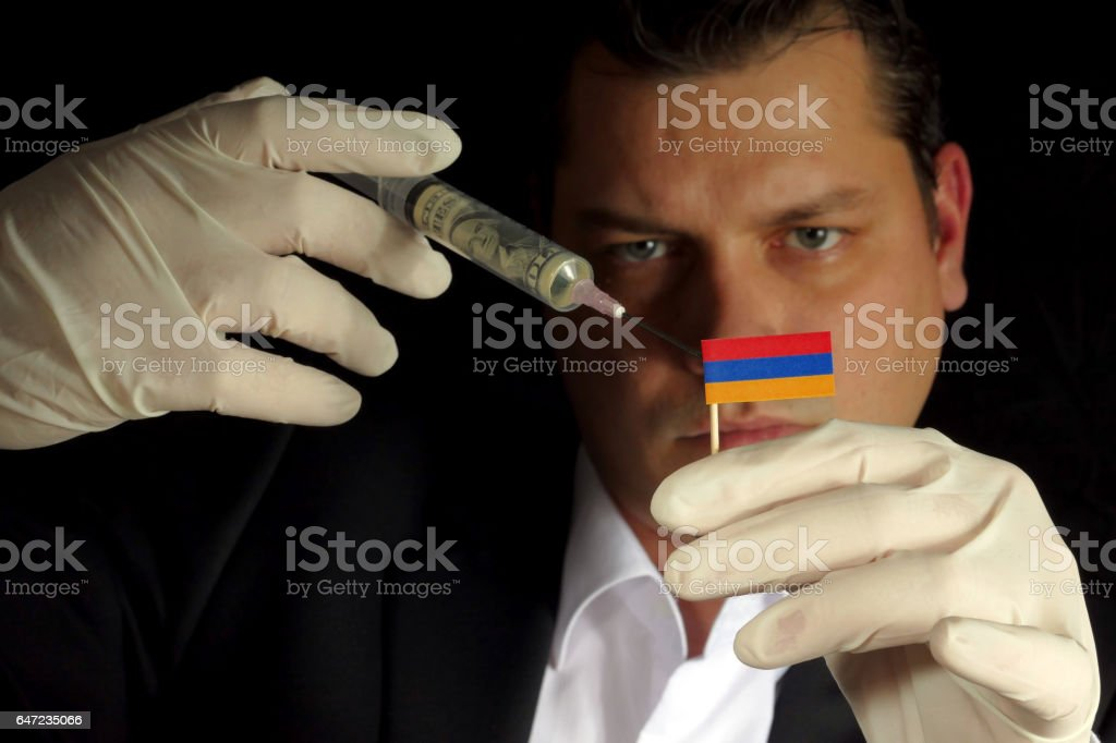 Young businessman gives a financial injection to Armenian flag isolated on black background stock photo