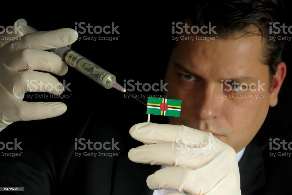 Young businessman gives a financial injection to Dominican flag isolated on black background stock photo